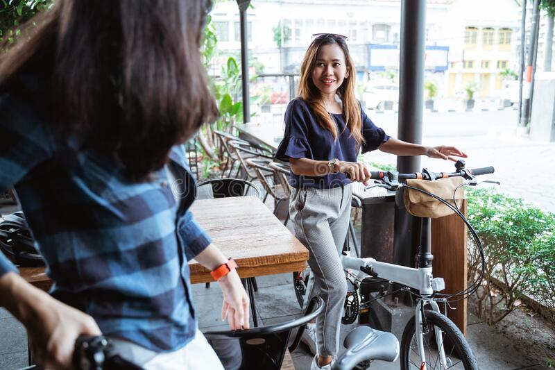 Two young women cyclists meeting at the cafe royalty free stock image
