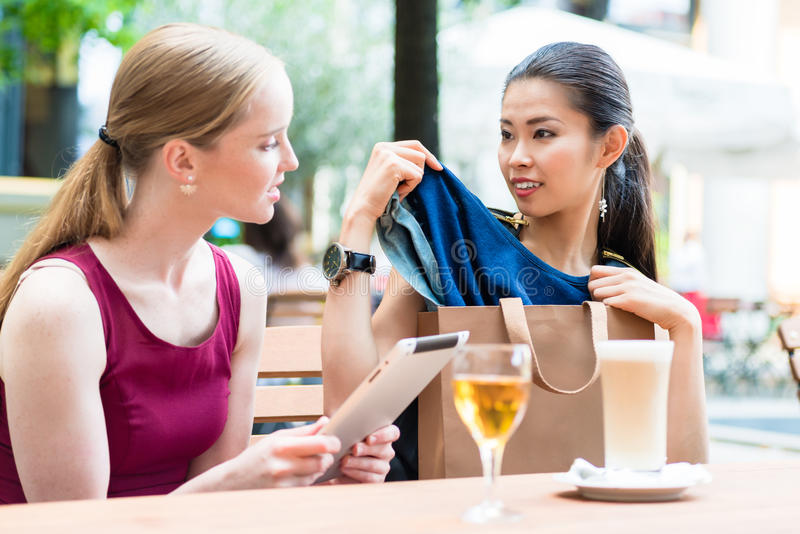 Two young women discussing a clothing purchase stock images