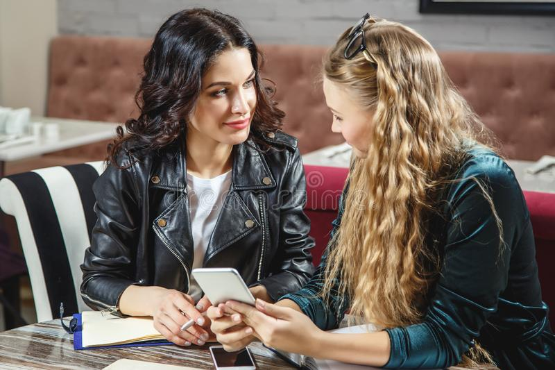 Two young women are discussing new projects while sitting in a cafe. Business meeting. royalty free stock photo