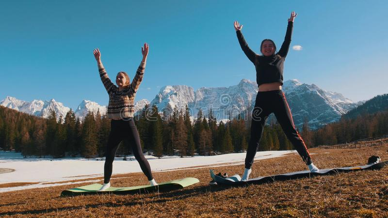 Two young women doing fitness outdoors - stand with their hands up - forest and mountains on a background. Mid shot stock photos