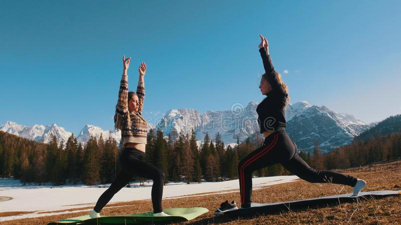 Two young women doing fitness outdoors - stretching and put their hands up - forest and mountains on a background stock image