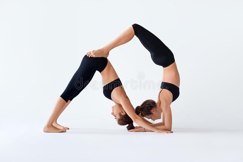 Two young women doing partner yoga asana Down Dog and Scorpion stock image