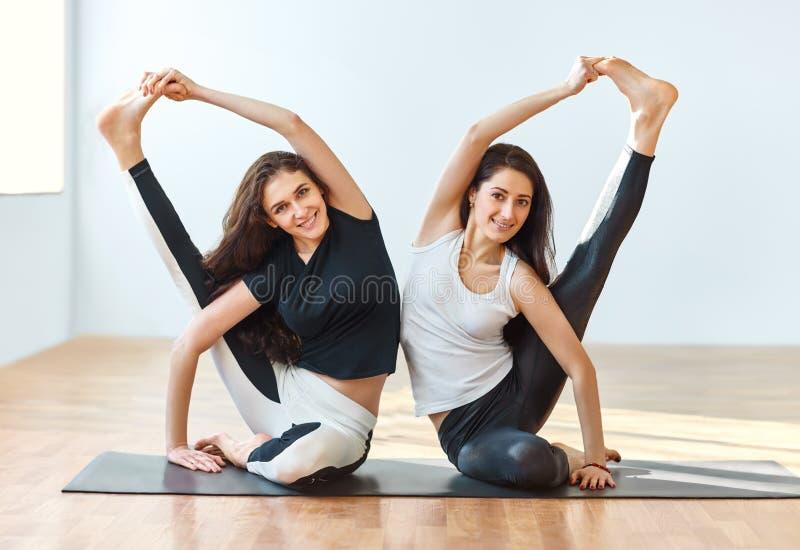 Two young women doing yoga asana compass pose. Parivrtta Surya Yantrasana stock photos