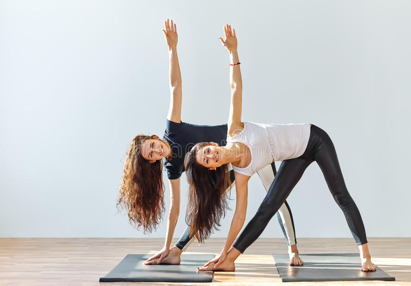 Two young women doing yoga asana extended triangle pose royalty free stock photos