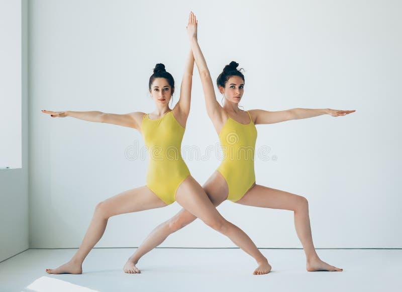 Two young women doing yoga asana Warrior II Pose stock photo