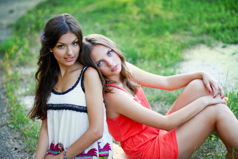Two young women in dresses. Sitting near royalty free stock photo