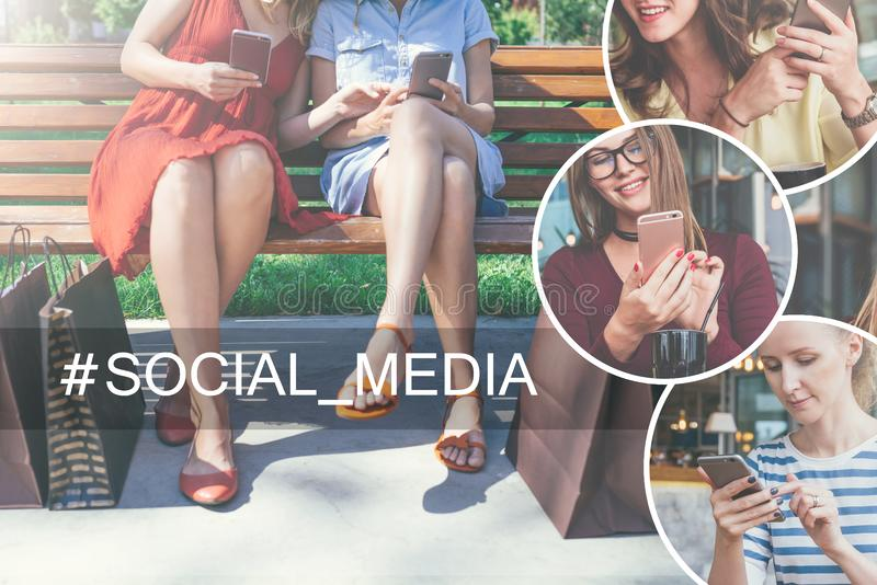 Two young women in dresses sitting on a park bench, using their smartphones. Nearby are shopping bags. stock images