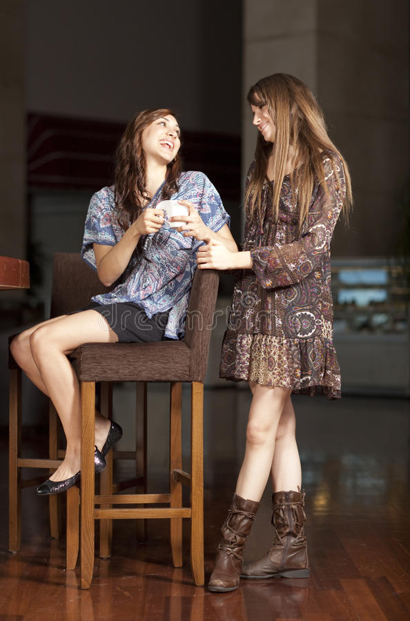 Two young women drinking coffee at a bar stock photography