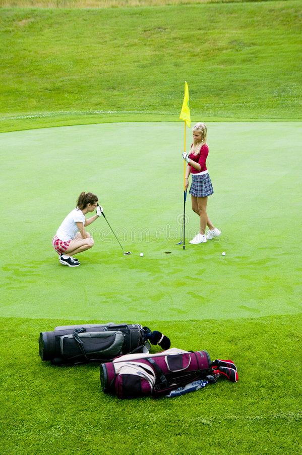 Download Two Young Women Enjoy A Game Of Golf. Stock Image - Image: 1540727