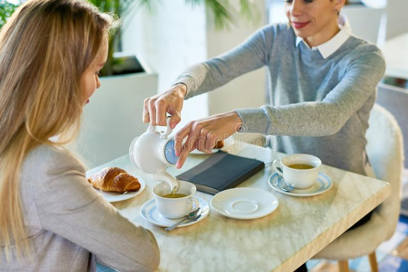 Two Young Women Enjoying Breakfast in Cafe. High angle view of two young women meeting during lunch break at cafe table enjoying tea and croissants royalty free stock photography