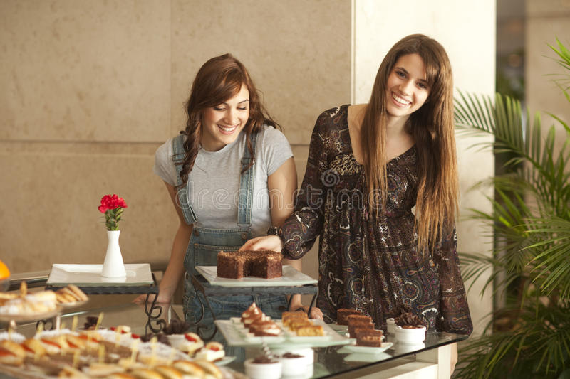 Two Young Women Enjoying A Dessert Buffet Royalty Free Stock Images