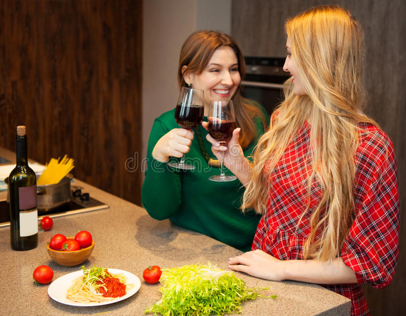 Two young women friends drinking red wine stock photo