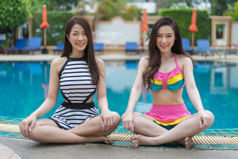 Two young women friends enjoy in swimming pool royalty free stock image