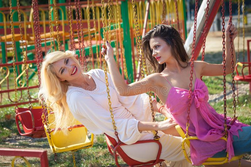 Two young woman have fun in amusement park royalty free stock photos