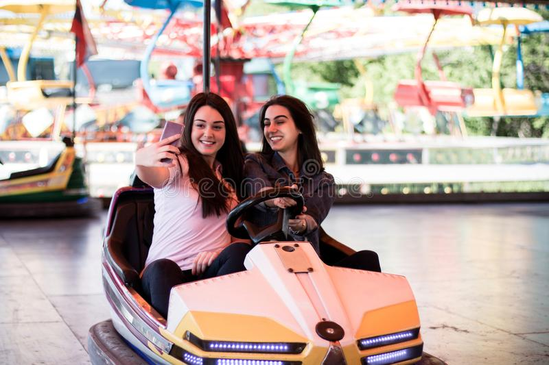 Young women having a bumper car ride. Two young women having a fun bumper car ride at the amusement park, laughing, enjoying themselves. Making a selfie stock photography