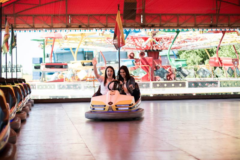 Young women having a bumper car ride. Two young women having a fun bumper car ride at the amusement park, laughing, enjoying themselves royalty free stock image