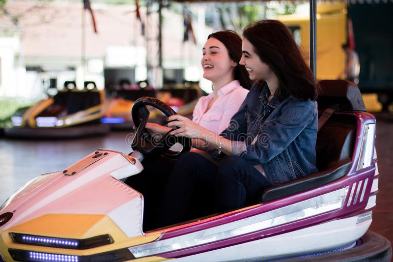 Young women having a bumper car ride. Two young women having a fun bumper car ride at the amusement park, laughing, enjoying themselves royalty free stock photos