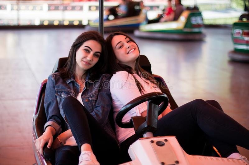 Young women having a bumper car ride. Two young women having a fun bumper car ride at the amusement park, laughing, enjoying themselves royalty free stock photo
