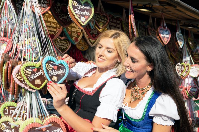 Girls on oktoberfest ore springfestival. 2 two young women are having fun at the Spring Festival, Oktoberfest, Oktoberfest, with gingerbread heart chocolate stock image