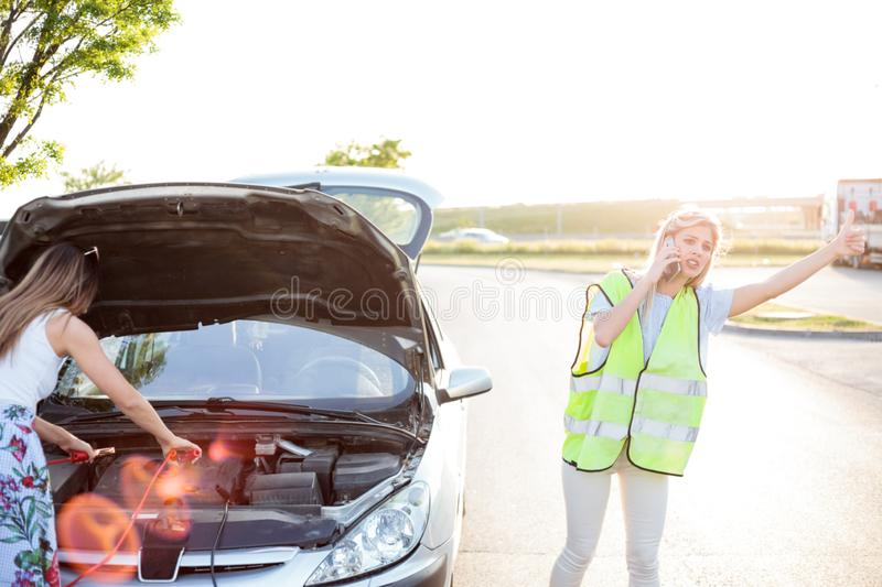 Two young women having problems with their car, being stranded on the side of the road stock photo