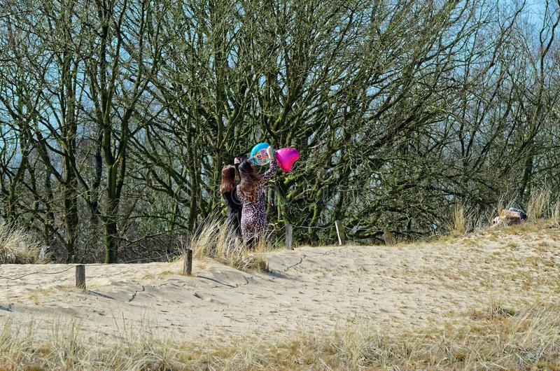 Two young women with helium ballons on a sandy dune royalty free stock photos