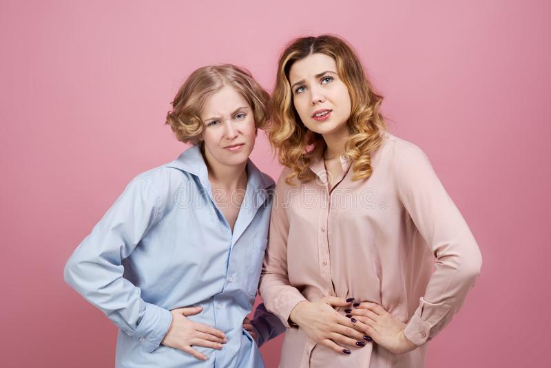 Two young women hold onto their bellies with suffering expression. Studio portrait on pink background. The concept of stomach trouble, menstrual pains royalty free stock photos