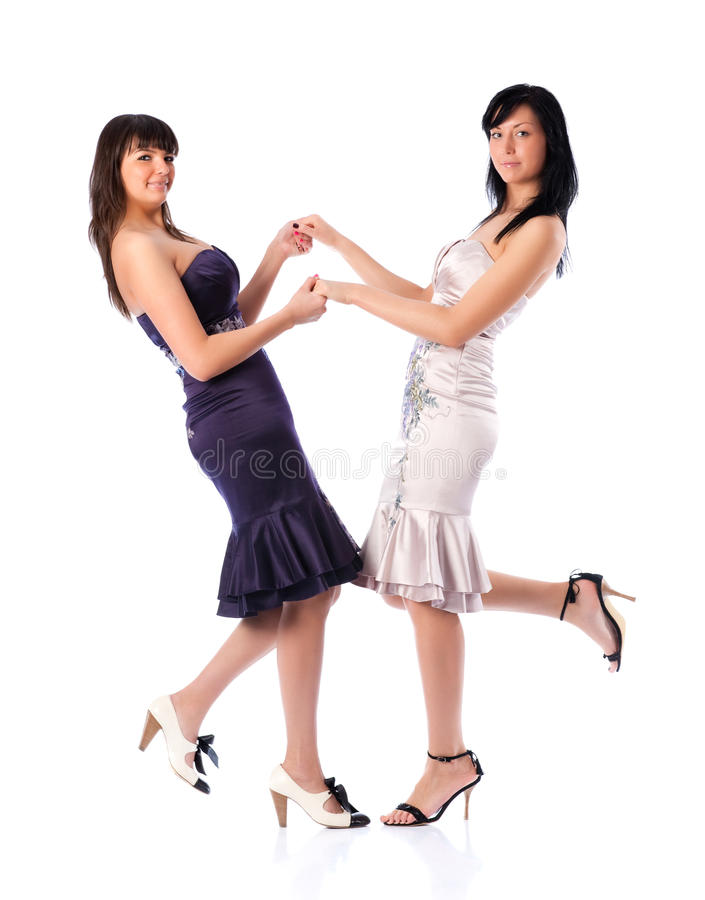 Two young women holding hands. Isolated on white stock photo