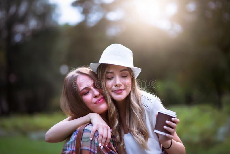 Two young women holding hands walking in green park. Best friends. Two young women best friends walking on summer day in green park royalty free stock photo