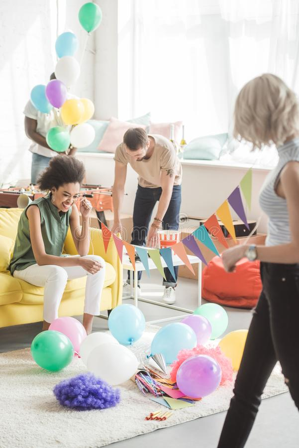 Two young women holding string with party garlands and their male friends decorating room. Behind stock image