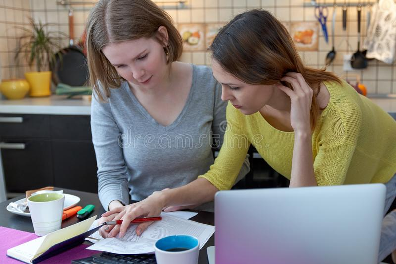 two young women housewife businesswoman student with joyful emotions manage budget, discuss account offers banks, financial royalty free stock images