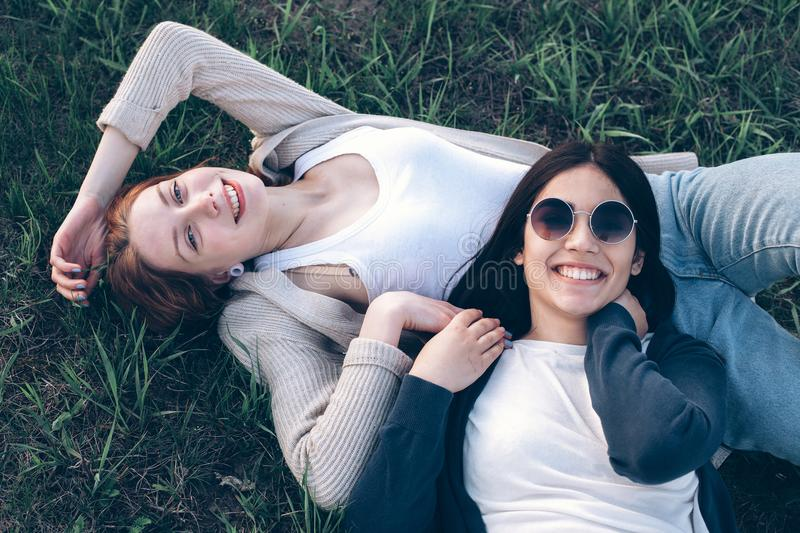 Two young women lie on the grass royalty free stock image