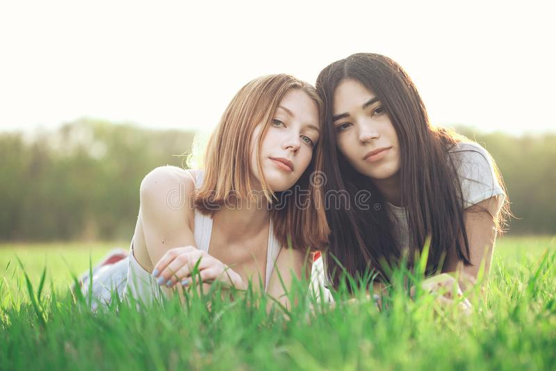Two young women lie on the grass stock photography