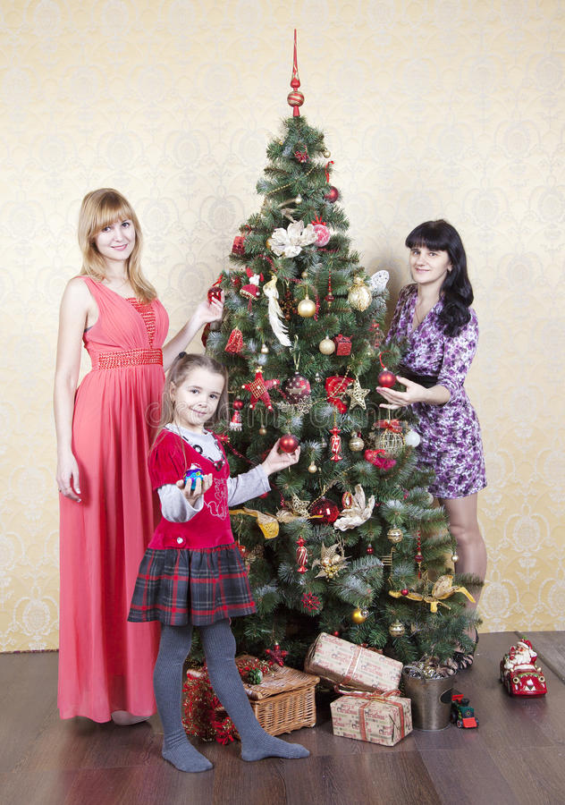 Two young women and little girl near a christmas tree stock image