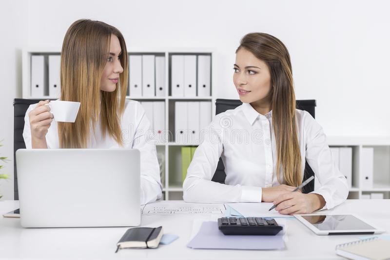 Download Two Young Women Looking At Each Other In Office Stock Photo - Image: 83722186