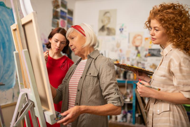 Two young women looking at famous artist painting on canvas. Looking at artist. Two young talented women looking at famous artist painting on canvas stock photo