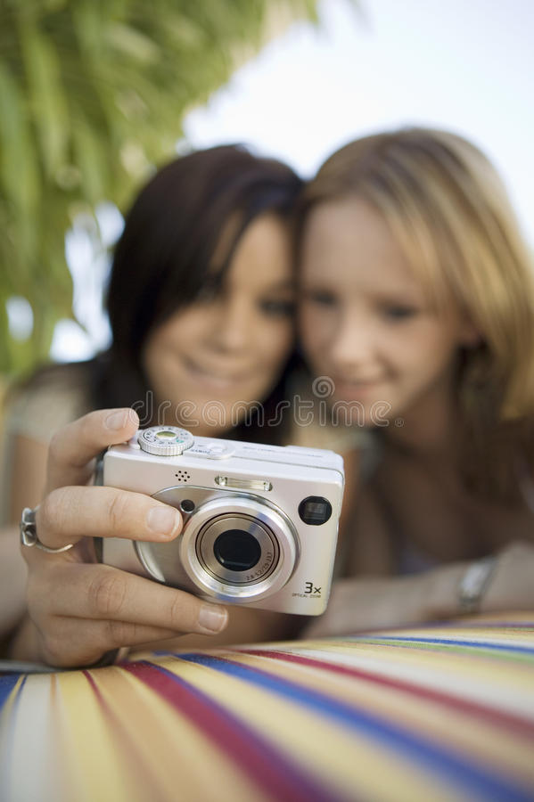 Download Two Young Women Looking At Pictures On Digital Camera In Backyard Focus On Camera Ground View Stock Photo - Image: 30840748