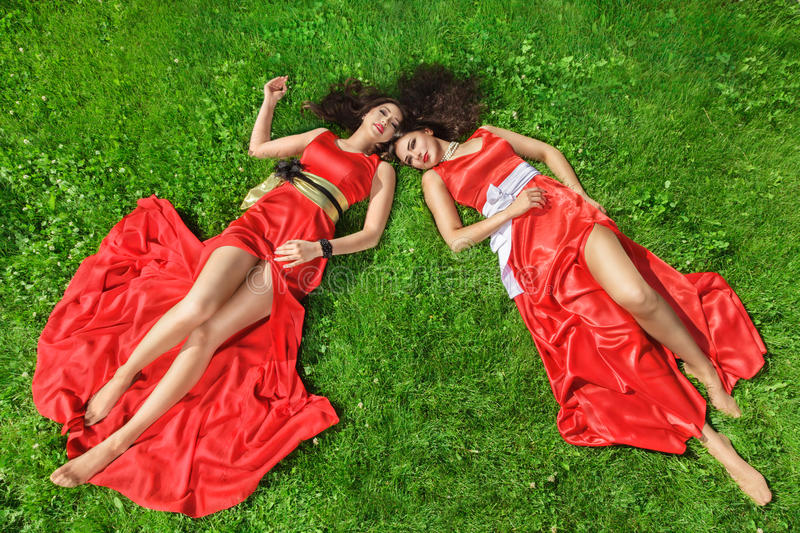 Two young women lying on grass royalty free stock photo