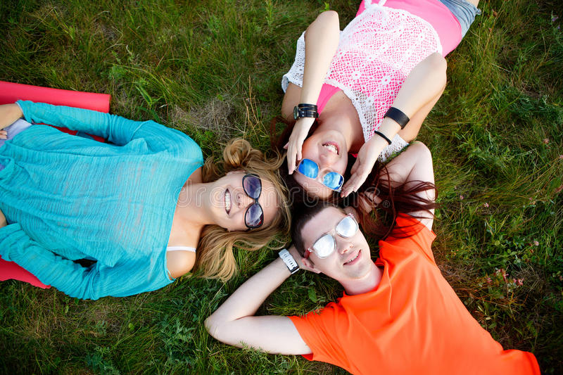 Two young women and man resting while lying on grass stock photo
