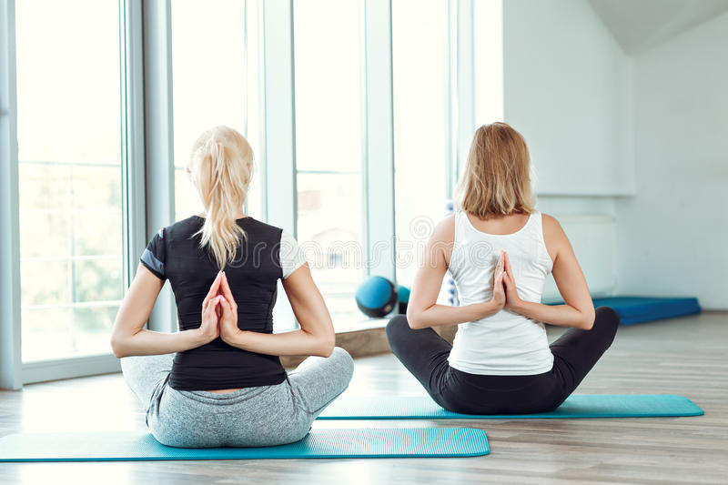 Two young women practicing yoga in gym. girl joining hands behind back. Two young women practicing yoga in the gym. girl joining hands behind her back stock photos