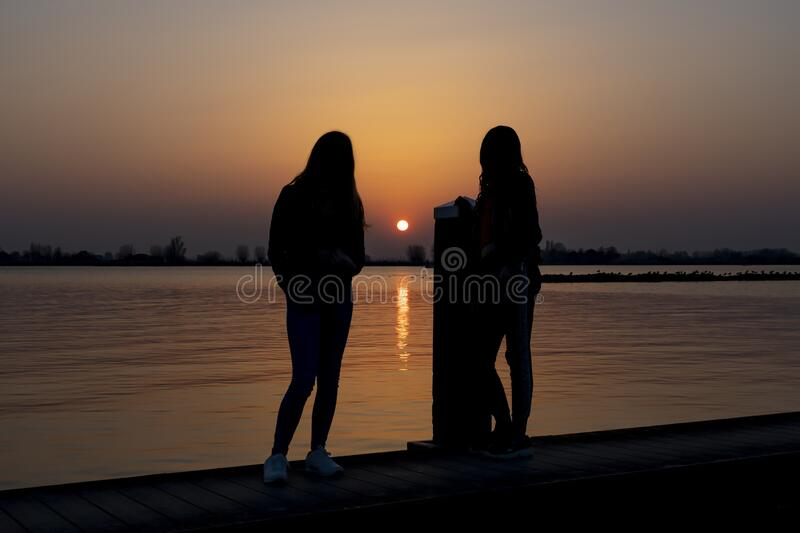 Two young women relaxing during  sunset on a landing stage at the Lake Zoetermeerse Plas in Zoetermeer, The Netherlands 2.  stock photography