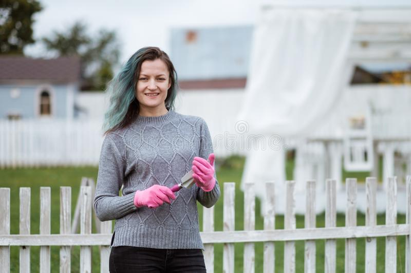 Young women in the background of a garden with gloves and tools with a field of beds royalty free stock image