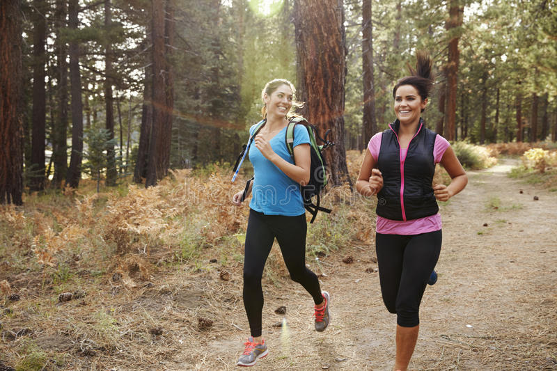 Two young women running in a forest, close up stock images