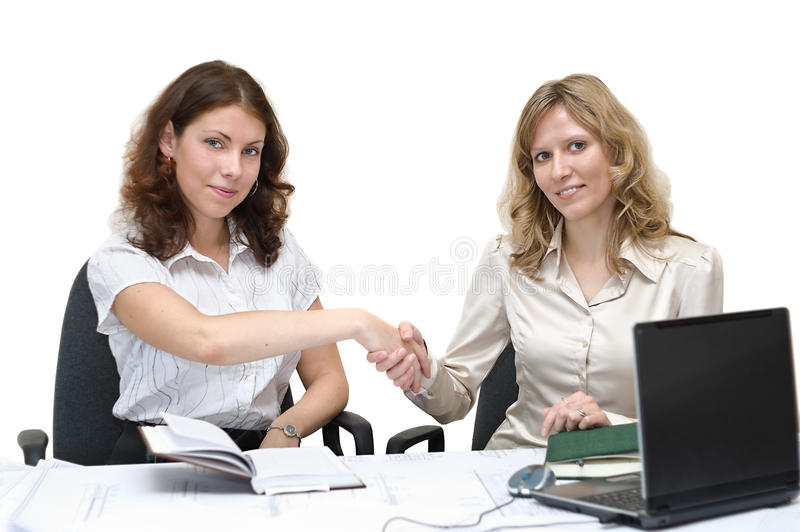 Two young women shaking hands. Two young business women shaking hands in office. Isolated over white background royalty free stock photo