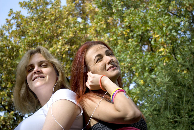 Two young women sharing music. And having fun in a park - concept of different taste in music stock images