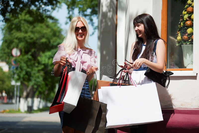Two happy fashion women with shopping bags walking in city street