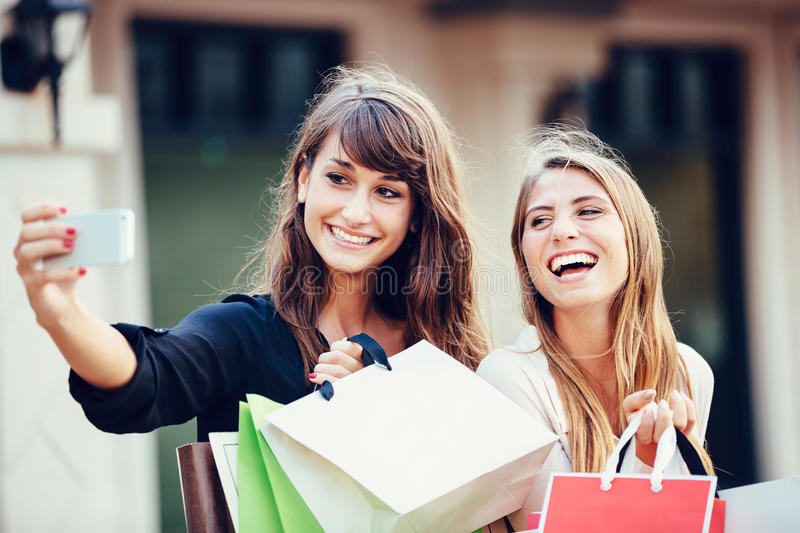 Two young women shopping at the mall taking a selfie. Or self portrait with their cell phone stock images