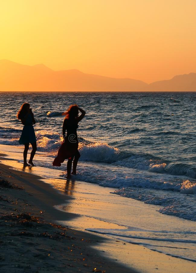 Two young women in silhouette on a sunset beach one posing for a photo against a beautiful orange evening sky royalty free stock photos