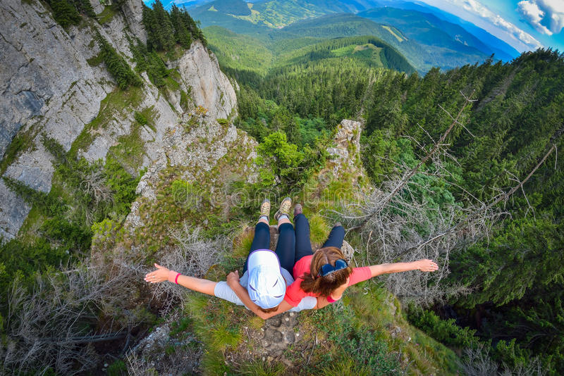 Two young women sitting on a cliff edge in the Ceahlau mountains in Romania. Two women sitting on a cliff edge in the Ceahlau mountains in Romania royalty free stock photos