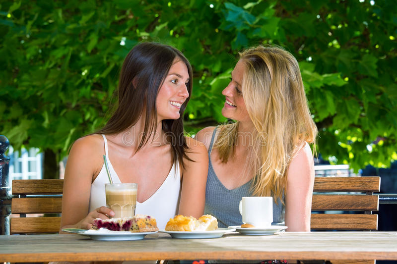 Two young women sitting close in outdoors cafe. Two pretty young women sitting close and looking at each other smiling, at street cafe table with coffee and royalty free stock images
