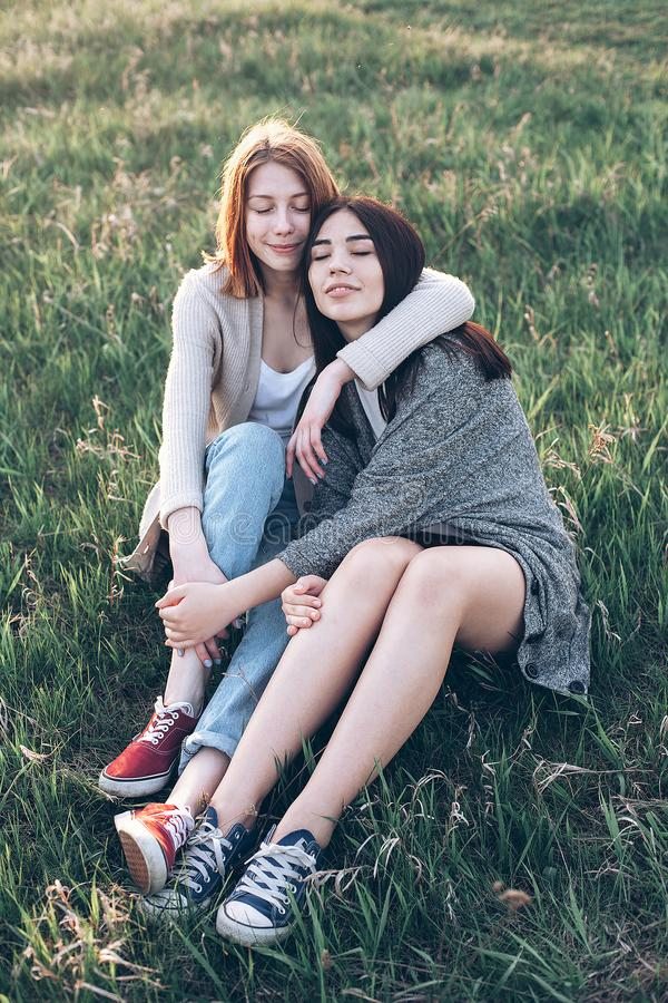 Two young women sitting on the grass stock images